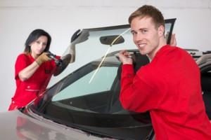 Glaser tauschen eine Windschutzscheibe an einem Auto aus